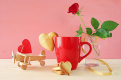 Cup of coffe with cookies next to one red rose in the vase. And plane, on wooden table Stock Image