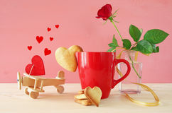 Cup of coffe with cookies next to one red rose in the vase. And plane, on wooden table Stock Images