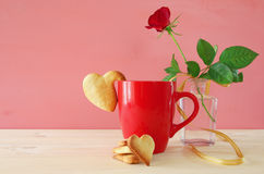 Cup of coffe with cookies next to one red rose in the vase. On wooden table Royalty Free Stock Images