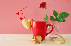 Cup of coffe with cookies next to one red rose in the vase. On wooden table Stock Images