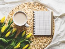 Cup of coffe with flowers and sketchbook. On bed, still life stock images