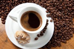 A cup and coffe with foam at the background of cjffee beans Royalty Free Stock Photo