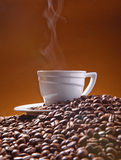 A cup and coffe with foam at the background of cjffee beans Stock Photography