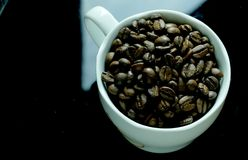 Cup of coffe full with beans. Cup of coffe full with coffe beans stock photography