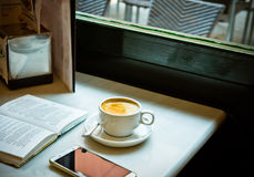 Cup of coffe with an open book and smartphone on a table by the window in a cafe Royalty Free Stock Image