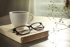 Cup of coffe on reading book  with glasses on table Stock Image