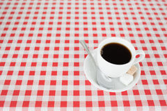 A cup of coffe on a tablecloth. In a kitchen Stock Image