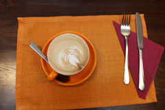 Cup of coffe on a tablecloth. Cup of coffe on a orange tablecloth in the cafe Stock Image