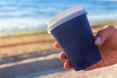Cup of coffe to go on the sea shore Royalty Free Stock Images