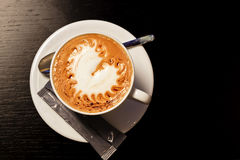 Cup of coffe on wood table. Heart shaped foam on top stock photography