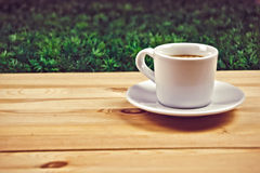 Cup of coffe on wooden table in garden Royalty Free Stock Photo