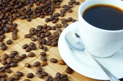 Cup of coffee. A white cup between brown coffee beans Stock Photography