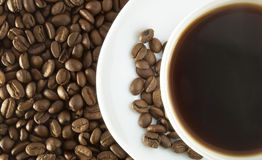 Cup of coffee. White cup of coffee on the heap of brown seed royalty free stock images