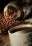 Cup of coffee. A cup of coffee isolated with a heap of coffee beans in mood lighting Stock Image