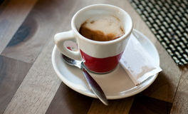 Cup of coffee. Closeup of cup of coffee on saucer next to spoon and sugar sachet Royalty Free Stock Images