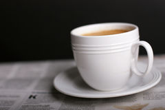Cup of coffee. Newspapers on black background Stock Photos