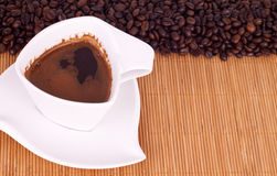 Cup of coffee. White cup of coffee on coffee beams - front view Royalty Free Stock Photos