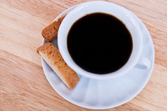 Cup of coffee. White cup of coffee with two biscotti close up Stock Photography