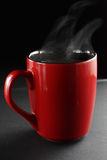 Cup of coffee. Red cup of coffe on a dark background royalty free stock images