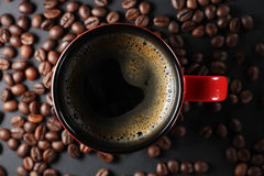 Cup of coffee. And a lot of beans around it royalty free stock image