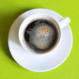 Cup of coffee. Coffee in white cup with white saucer on green background royalty free stock photo