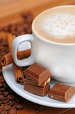 Cup of coffee. With chocolate, cinnamon sticks and coffee beans Royalty Free Stock Images