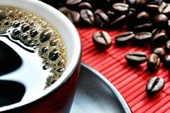 Cup of coffee. Black cup of coffee on the red mat Stock Photo