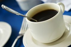 Cup of coffee. Closeup image of a cup of coffee on blue tablecloth stock image