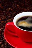 Cup of coffee. Red cup with coffee on coffeebeans royalty free stock image