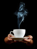 Cup of coffee. In the women's hand on black background Stock Images