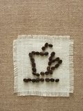 Cup of coffee. Drawing of coffee cup by coffee seed on the sackcloth Stock Photos