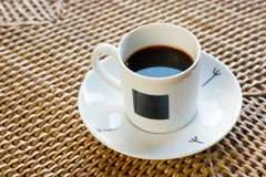 Cup of coffee. White cup of coffee in rattan Royalty Free Stock Image