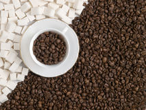 A cup of coffee. Background of a cup of coffee beans with lumps of sugar Stock Image