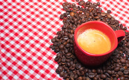 Cup of Coffee. And Coffee Beans on Red Gingham cloth Royalty Free Stock Photography