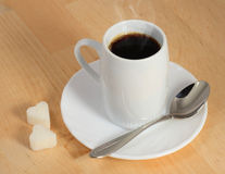 Cup of coffee. Spoon and two slices of sugar on a wooden table Royalty Free Stock Photo