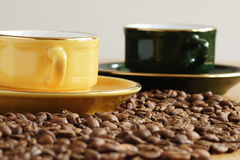 Cup of coffee. Yellow and green cups and grains of coffee Stock Images