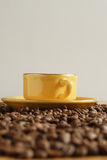 Cup of coffee. Yellow cup and grains of coffee Royalty Free Stock Image