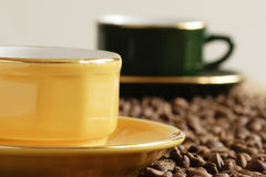 Cup of coffee. Yellow cup and grains of coffee Stock Images