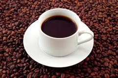 Cup of Coffee. Black coffee in a white cup and saucer, on a bed of coffee beans Royalty Free Stock Image