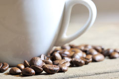 A cup of coffee. Coffee beans at wooden plate stock photos