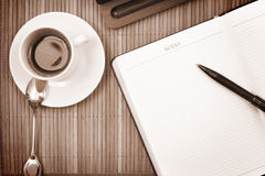 Cup of coffee. With notepad on the table Royalty Free Stock Photography