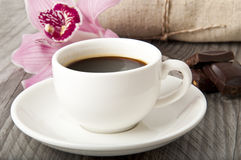 Cup of coffee. Chocolate and orchid on wooden background Royalty Free Stock Image