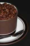 Cup of coffee. Cup full of coffee beans. Placed on saucer with stainless steel spoon royalty free stock photography