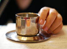 Cup of coffee. Hand and metallic cup of coffee Royalty Free Stock Photography