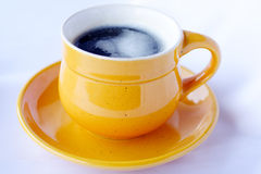 Cup of coffee. In yellow dishes on white background royalty free stock image