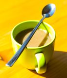 Cup of coffee. With a spoon balanced on top. Saturated colors Stock Image