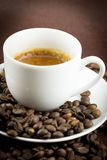A cup of coffee. With some coffee beans royalty free stock photography