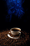 Cup of coffee. The cup of coffee and grains on are black - a dark blue background Royalty Free Stock Photo