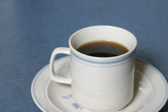 Cup of coffee. On a blue surface Stock Photos