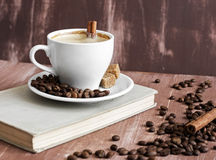 Cup of coffee. With cinnamon and sugar and book royalty free stock photo